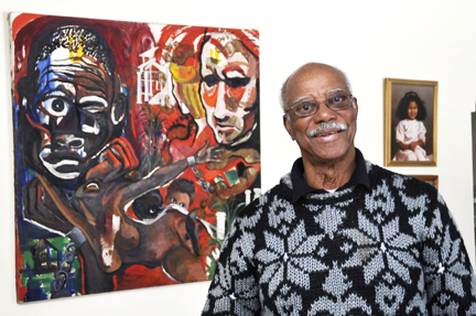 Dr. Lancelot Thompson posed by a painting that he says represents the history of blacks and whites in Jamaica, the country where he was born.