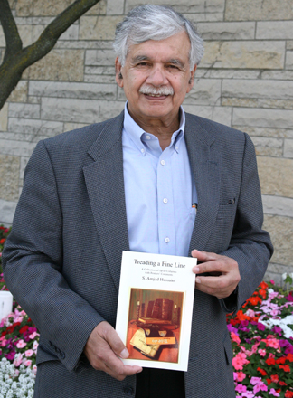"Dr. S. Amjad Hussain posed for a photo with his new book, ""Treading a Fine Line."""