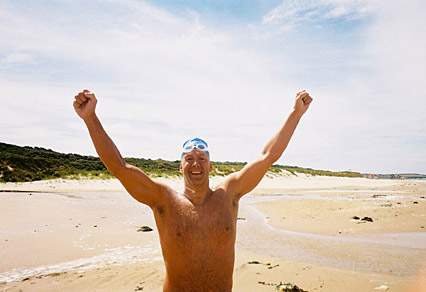 John Muenzer raised his arms triumphantly on a beach in Wissant, France, after swimming the English Channel.