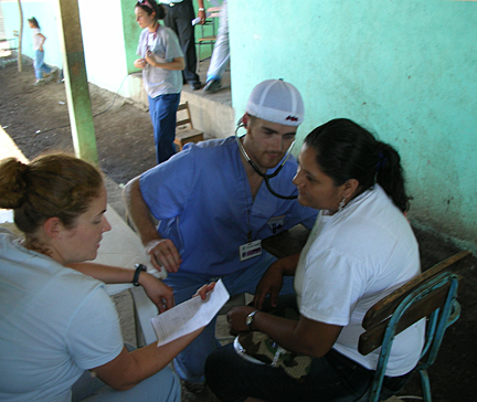 William Schmitt listened to the heart of a patient in Nicaragua as Dr. Anna Rohrbacher reviewed information.