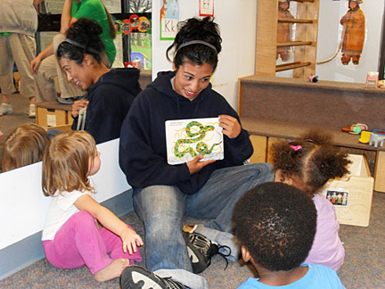 Senior catcher Mica Sanchez read to children at Apple Tree Nursery School.