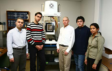 Posing by a high-frequency temperature-controlled test instrument that is used to characterize thermomechanical and fatigue behavior of nitinol devices are, from left, Dr. Mohammad Elahinia; Majid Tabesh and Walter Anderson, master's students in mechanical engineering; Shuo Wang, an electrical engineering doctoral student; and Minal Bhadane, a biomedical engineering doctoral student.