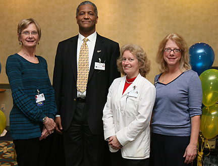 Mark Chastang posed for a photo with, from left, Sandra Gardam, Jane Lawrence and Katie Roberts who were recognized for perfect attendance in 2009.