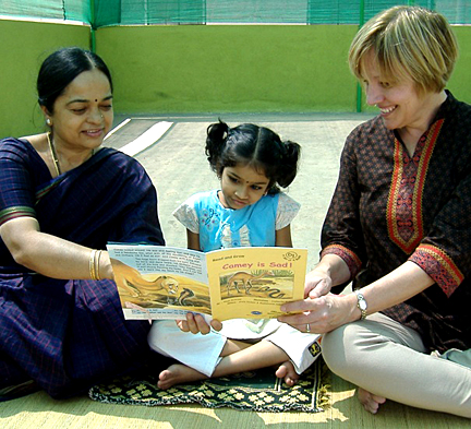 Dr. Joan Kaderavek, right, and Dr. Prima Rao read with Navya Sajja at Blooming Buds in Mysore, India.