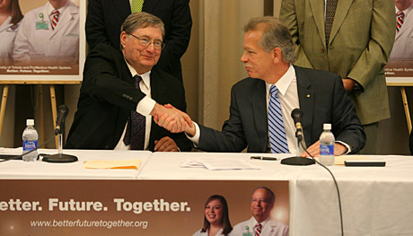UT President Lloyd Jacobs, left, shook hands with Randy Oostra, president and chief executive officer for ProMedica, after the two signed an agreement for the University and ProMedica Health System to become partners.