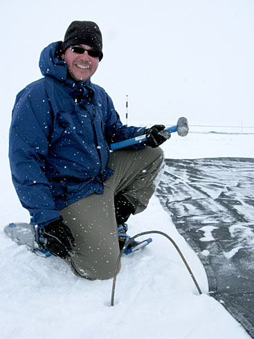 Dr. Mike Weintraub took a break from installing stakes to hold down the black cloth used to accelerate snow melt in the Arctic.