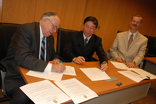 Dr. Thomas Gutteridge, dean of the UT College of Business Administration, left, and Dr. Wang Xiangyao, dean of the School of Accounting at Zhejiang University of Finance and Economics, signed an agreement earlier this month as Dr. Donald Saftner, right, UT professor and chair of accounting, looked on.