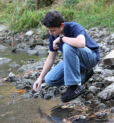 Alfonso Zapata, who attends Toledo Early College High School, collected a water sample from the Ottawa River as part of the Student Watershed Watch.