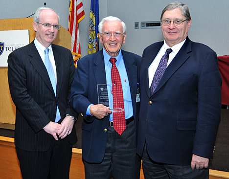 Dr. Maurice Manning showed off the award he received for 40 years of service while posing for a photo with Dr. Jeffrey Gold, left, and President Lloyd Jacobs.