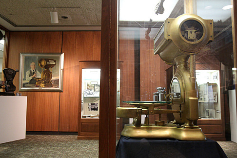 """This gold Toledo Scale from around 1929 is seen in Georges LaChance's painting titled """"O.N. Teall — Final Inspection."""" Both are part of the """"Wholly Toledo"""" exhibit; the painting belongs to the Canaday Center, and the scale is on loan from the Maumee Valley Historical Society."""