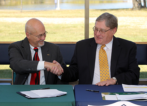 UT President Lloyd Jacobs, right, and Northwest State Community College President Thomas Stuckey shook hands after signing an agreement Friday at the Scott Park Campus of Energy and Innovation to establish a new associate's degree in alternative energy technologies. The degree will be from Northwest State with students taking classes from both institutions at Scott Park.