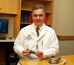 Dr. Francis Pagani holds a HeartMate II heart-assisting device, which was approved by the FDA in 2008 after a national clinical trial that he helped lead. On the table is an earlier-generation device, the HeartMate.
