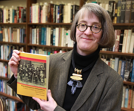 Barbara Floyd holds a copy of the book she edited.