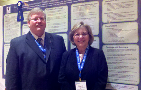 Dr. Timothy Gaspar, dean of the UT College of Nursing, and Cheryl Gies posed for a photo by her poster at the conference.