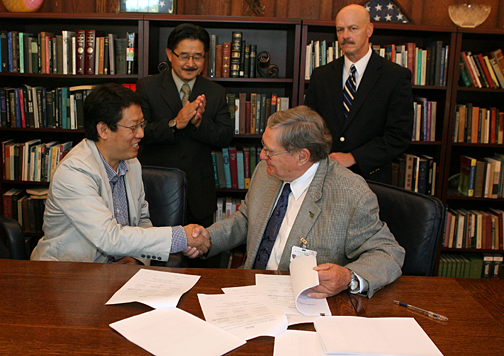 President Lloyd Jacobs, right, shook hands with Dr. Dong-Shik Kim, UT associate professor of chemical and environmental engineering, after signing a cooperative research and development agreement with Kwangwoon University in South Korea and the Air Force Institute of Technology. Also on hand for the ceremony were Dr. Do-Young Yoon, professor of chemical engineering at Kwangwoon University, left, and Dr. James Trempe, UT vice president for research.