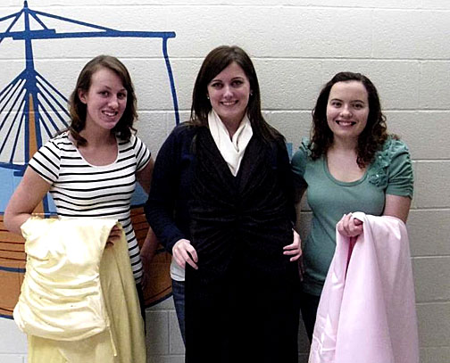 Students, from left, Charlotte Cox, Ashley Wickerham and Chelsea Alexander show off some of the dresses they've collected for Once Upon a Prom.
