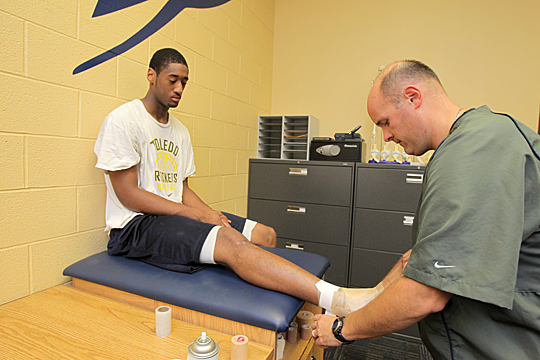 Brian Jones, UT assistant athletic director for sports medicine, taped the ankle of basketball player Matt Smith.