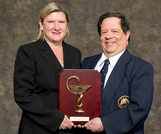 Dr. Ken Alexander received the Ohio Pharmacists Association's 2013 Bowl of Hygeia award for outstanding community service from Cindy Arnett of Boehringer Ingelheim Pharmaceuticals Inc.