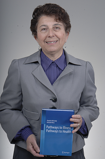 "Dr. Angele McGrady holds a copy of her new book, ""Pathways to Illness, Pathways to Health."""