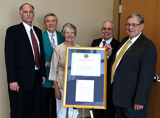 Posing for a photo with the plaque signifying Leadership in Energy and Environmental Design certification from the U.S. Green Building Council for the Savage & Associates Complex for Business Learning and Engagement are, from left, Dr. Thomas Sharkey, Robert Savage and his wife, Susan Savage, Dr. Thomas Gutteridge and President Lloyd Jacobs.