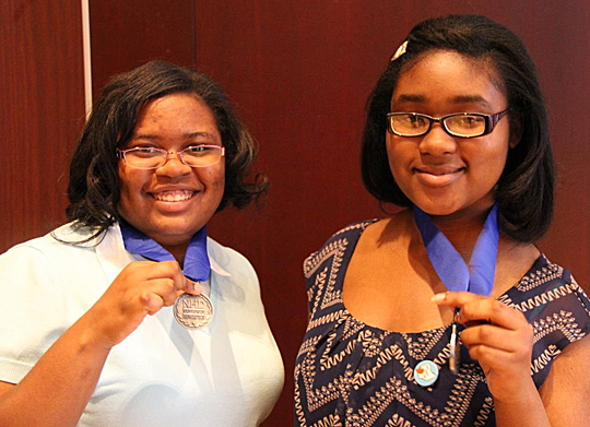 Delaina Lane, left, and Brianna Frazier showed off the medals they won in a regional competition in Columbus to advance to the Kenneth E. Behring National History Day Contest in Washington, D.C.
