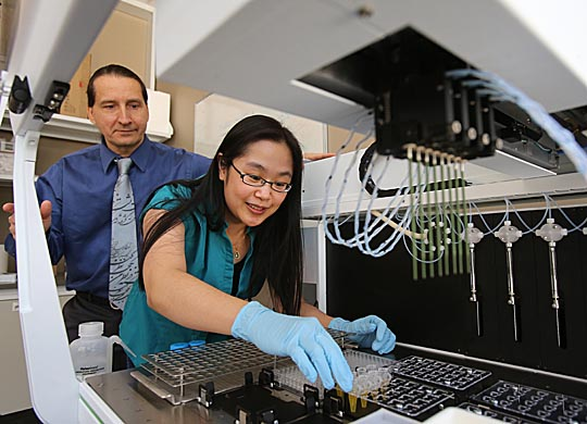 Dr. David Giovannucci and his research associate, Muncharie Brooke Saepoo, loaded saliva samples into an automated liquid handler for biomarker analysis.