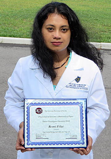Resmi Pillai shows the Junior Investigator Award from the American Physiological Society.