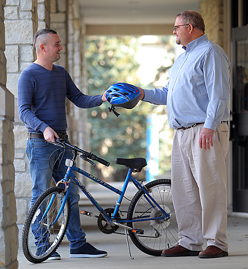Pete Thomas, who started Rocket ReCycle, handed a bike helmet to student Ivan Tkachenko.