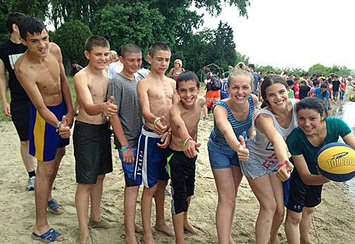 Volunteer Maria Antonov, holding the ball, and the campers at New Hope Moldova had fun on the beach.