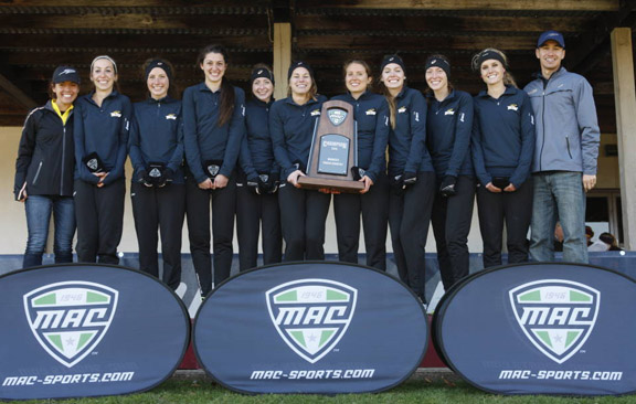 The women's cross country team posed for a photo with the trophy after winning the Mid-American Conference Championship. Head Coach Linh Nguyen, right, was named women's cross country coach of the year in the conference.