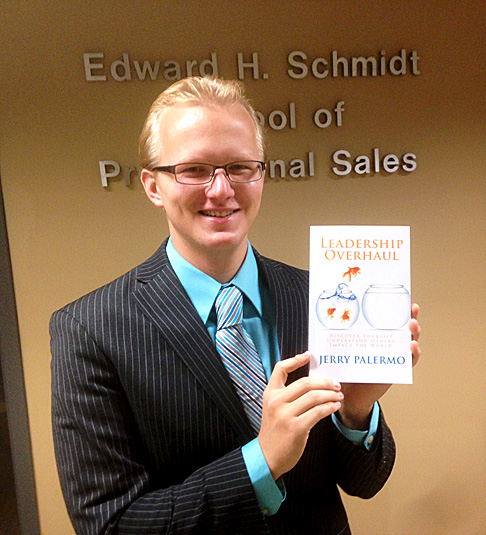 "UT business student Jerry Palermo holds a copy of his book, ""Leadership Overhaul: Discover Yourself, Understand Others, Impact the World."""