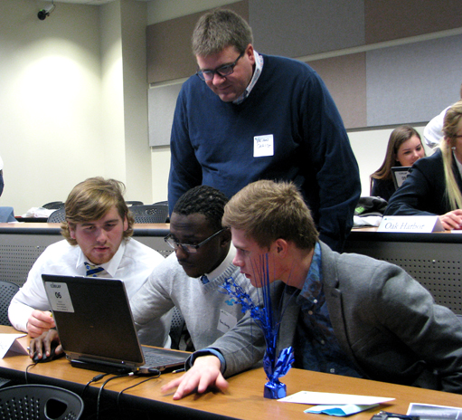 A mentor worked with local high school students during the Junior Achievement Business Challenge, which was held last month on Main Campus.