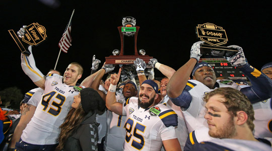 The Toledo Rockets hoisted the GoDaddy Bowl trophy after defeating Arkansas State, 63-44, Sunday night in Mobile, Ala.