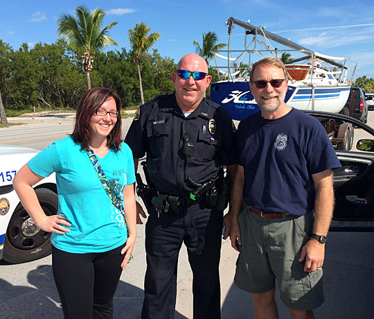 Misty Matter and Al Newell posed with Key West Police Officer Bob Bulnes on the shoulder of Florida State Road A1A in Key West Jan. 17.