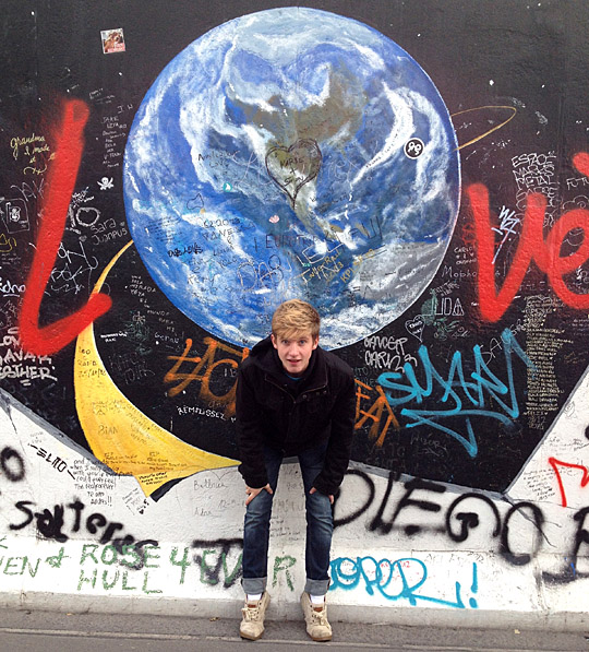 Neil Hetrick posed for a photo in front of the East Side Gallery in Berlin, Germany.