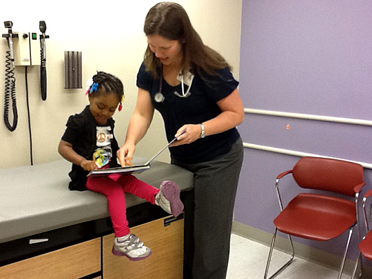 Dr. Mary Beth Wroblewski, assistant professor, assistant dean for student affairs, and pediatric clerkship director, gave a book to a young patient.