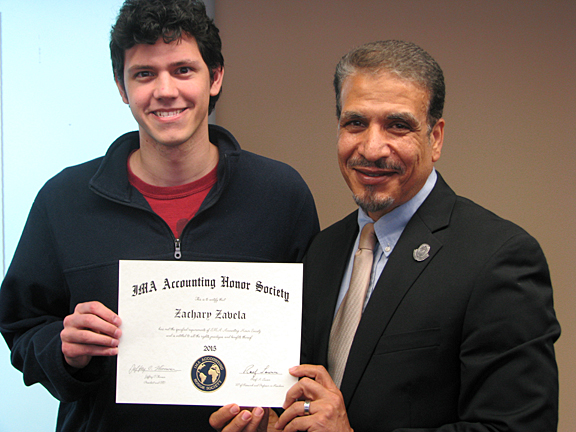 Dr. Hassan HassabElnaby, professor and chair of the Accounting Department, presented an honor society certificate to Zachary Zavela.
