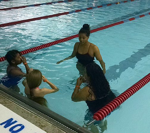 Zhada Fields spoke with three girls about how to swim during the Josh Project's June 18 lesson at St. Francis de Sales High School.