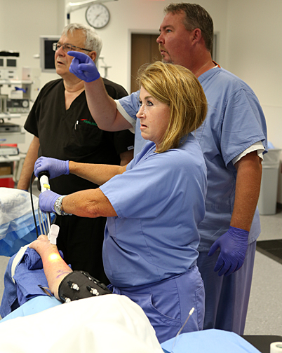 Julie Nelson practiced radial artery harvest surgery on a cadaver as Gary Tindel, center, noted how the technique was proceeding on the screen as Larry Pizzola watched. The training was being conducted by Ann Arbor-based Terumo, which visited the Jacobs Interprofessional Immersive Simulation Center last month.