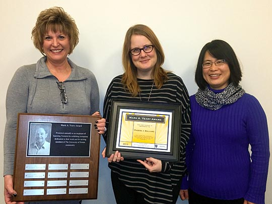 Phoebe Ballard, director of instructional design and development, center, showed off the Mark A. Yeary Award she was presented by Dr. Barbara Kopp Miller, associate provost for online education, who held the plaque where Ballard's name was added, and Dr. Mingli Xiao, senior instructional designer.