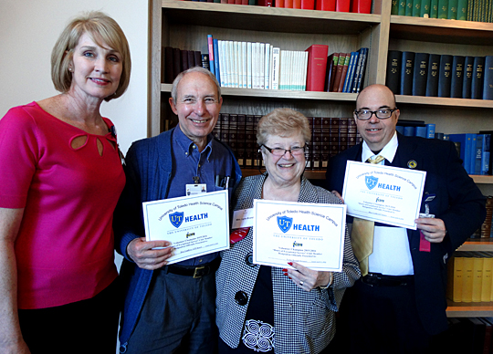 Patty MacAllister, support services coordinator, left, handed out certificates to, from left, Dr. Don Godfrey, UT professor emeritus of neurology, Lynn Brand, president of the Satellites Auxiliary, and Don Lemle, who were recognized at the UTMC Volunteer Luncheon for completing more than 500 service hours in 2015.