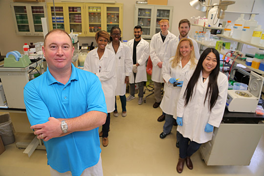 Dr. Terry Hinds Jr., left, is assisted in the lab by, from left, Assumpta Nwaneri, Imani Driskell, Vikram Sundararaghavan, Kevin Stephenoff, Lucien McBeth, Kari Neifer-Sadhwani and Justina Tain.
