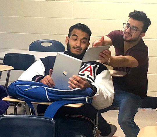 Mohammed Alabbas, right, showed his Sit&Tell story to Mahdi Ghashi. Both are advanced American Language Institute students who were in the Advanced Speaking and Listening class spring semester.