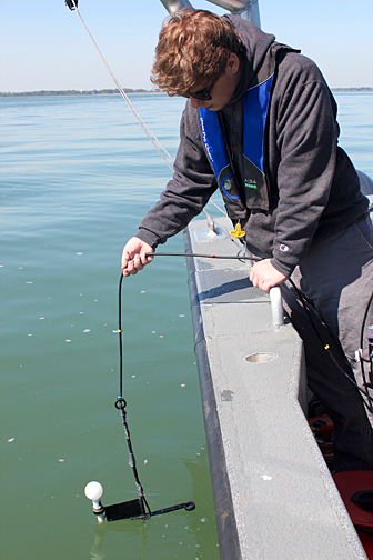 Zach Swan lowered the light meter into the water to measure how far light penetrates into the water.