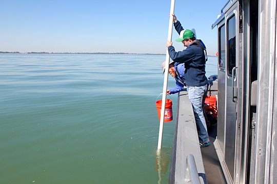Ken Gibbons pulled up a water sample using a a long, white tube that reaches the lake bottom. The water was emptied into the orange bucket held by Dr. Thomas Bridgeman.