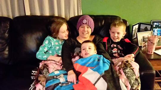 UT employee and cancer survivor Wendy Howe snuggles with the youngest members of her care team, her children, Abby, Ben, center, and Caleb.