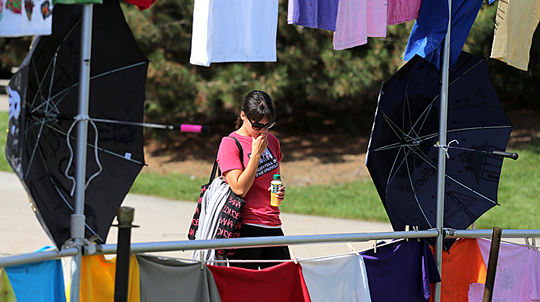 A student looked at the Clothesline Project and umbrellas that were on Centennial Mall for RAINN Day in 2014.