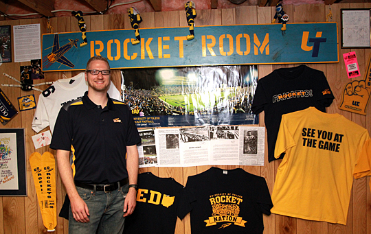Donovan Nichols stood beneath the sign that inspired his Rocket Room. As an undergraduate in 2002, he picked up the sign that hung in Rocky's Attic during the 1980s.