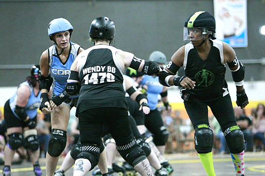 GunSmoke, a.k.a. Ulonda Sweeney, lined up with teammate Wendy Boughbreaks to block a Central Ohio Roller Derby jammer during a bout this summer.