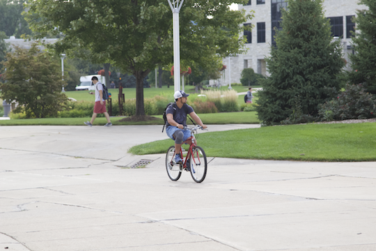 A student rode his bike in Centennial Mall.